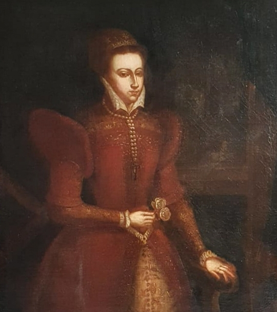 Follower of Federico Zuccaro, traditionally identified as Mary Queen of Scots. Mary stands one arm on the throne, in front of mullioned windows behind which stands a church. She is wearing a fine red gown with golden brocade, a double string of pearls ending in a crucifix, and holding two roses.